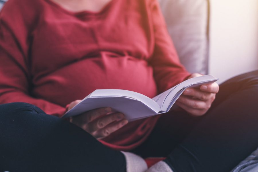 Pregnant woman reading book about pregnancy and maternity in living room, selective focus